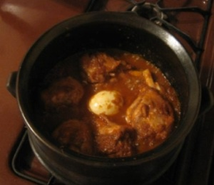 Doro wot cooking in a shakla dist,  a traditional Ethiopian clay pot