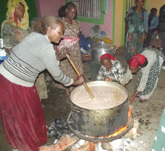 Women in Ethiopia cooking a huge pot of onions