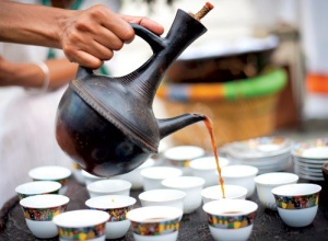 Coffee being poured from a jebena into a sini