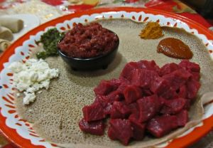 Ethiopians love their raw meats. Pictured here is  gored gored (foreground) and kitfo (background).