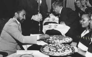 Emperor Haile Selassie enjoys a meal in 1954.  Neither the food nor the guests are Ethiopian.